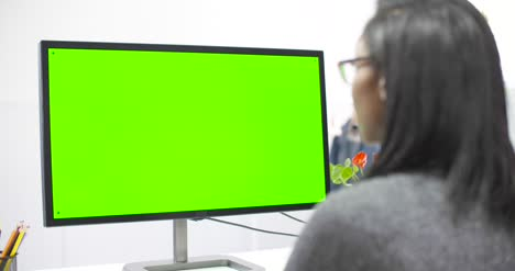 Tracking-Past-Woman-Working-at-Computer-Chroma-Screen