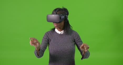 Young-Woman-on-Green-Screen-Gesturing-with-VR-Headset