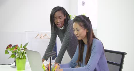 Two-Young-Women-Collaborating-in-Office