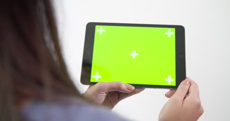 Young-Woman-Gesturing-on-Green-Screen-Tablet