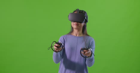 Young-Lady-Playing-VR-Game-in-front-of-Green-Screen
