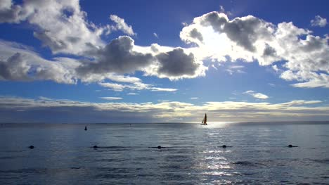 Silhouetted-Sailboat-Under-Blue-Skies