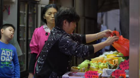 Lady-Weighing-Fruit-at-a-Market-Stall