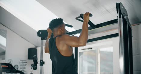Man-Doing-Pull-Ups-in-Gym