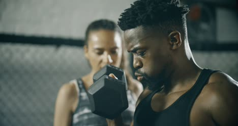 Man-Working-with-Personal-Trainer-in-Gym