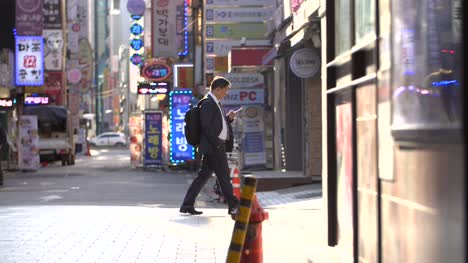 Businessman-Walking-Past-Neon-Signs