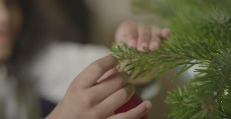 CU-Childs-Hands-Decorating-Christmas-Tree-1