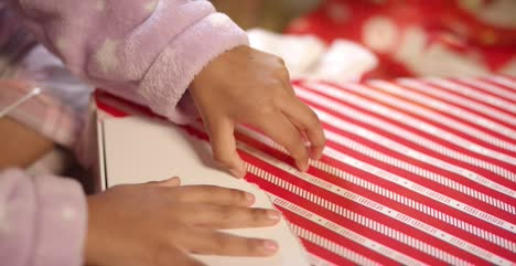 Child-Unwrapping-Present-Close-Up