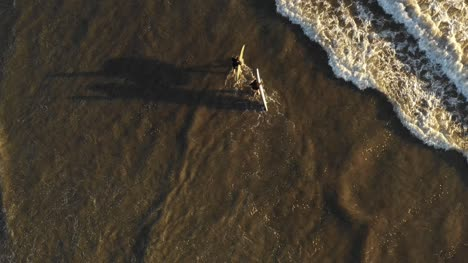 Surfers-Walking-in-Surf-Aerial