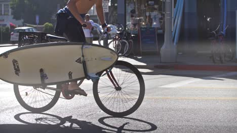 Man-Cycling-With-a-Surfboard