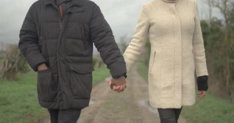 Couple-Holding-Hands-Approach-Camera