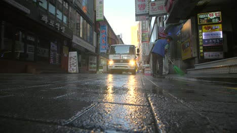Man-Sweeping-Street-at-Dawn