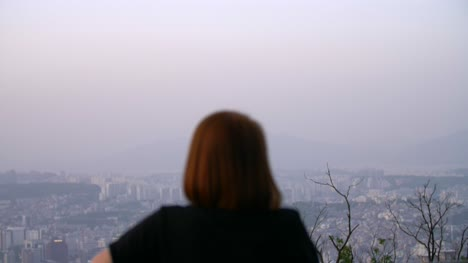 Woman-Looking-Out-Over-Seoul-Skyline