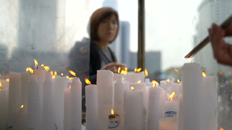Woman-Lighting-a-Candle-at-a-Shrine