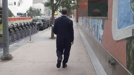 Businessman-Walking-On-Pavement