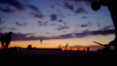 Silhouetted-Skateboarder-Passing-at-Sunset