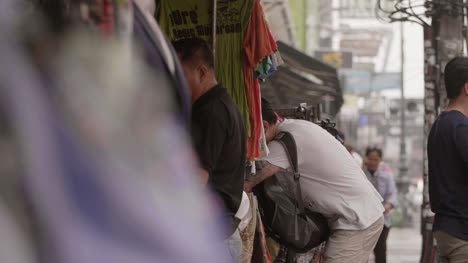 Man-Examining-Clothing-at-Bangkok-Stall