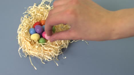 Placing-Easter-Egg-in-Straw-Nest