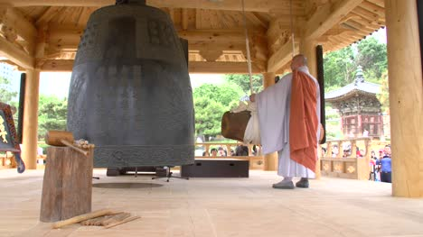 Buddhist-Monk-Striking-Large-Bell
