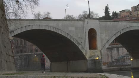 Walking-Under-Bridge-At-Dusk