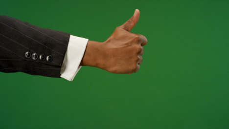 Male-hand-making-thumbs-up-gesture-on-green-screen