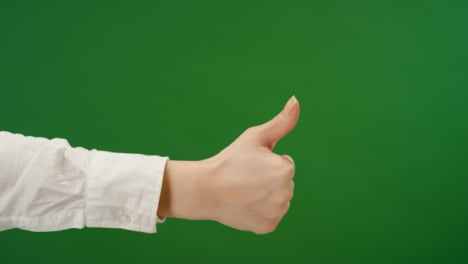 Female-hand-making-thumbs-up-gesture-on-green-screen