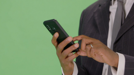 CU-Businessman-texting-on-teléfono-with-green-screen