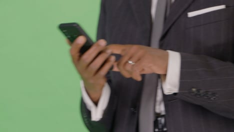 CU-Businessman-texting-while-walking-on-green-screen
