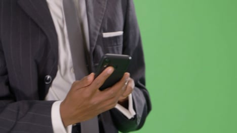 CU-Texting-Businessman-walking-towards-camera-on-green-screen