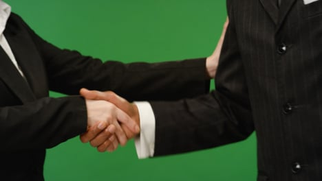 CU-Two-people-in-suits-shake-hands-on-green-screen