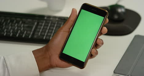CU-Man-tapping-on-phone-with-green-screen