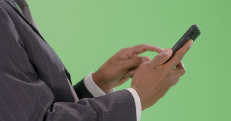 CU-businessman-typing-on-phone-with-green-screen