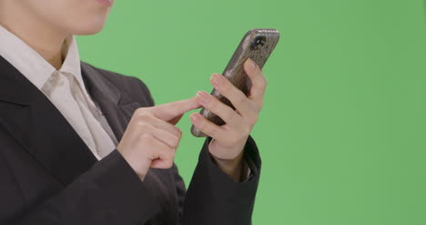 CU-Businesswoman-sending-email-on-phone-with-green-screen