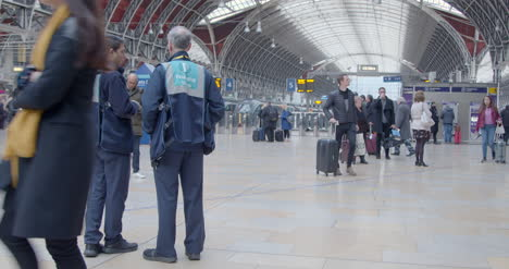 Two-train-stewards-stands-as-people-pass-through-station