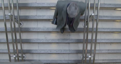 Man-walking-down-stairs-from-overhead