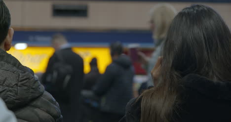 Woman-puts-on-earphones-in-train-station-with-people-passing