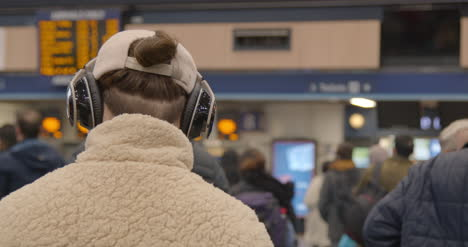 Man-wearing-headphones-in-crowded-train-station