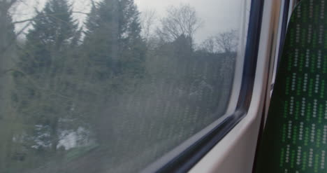 Looking-out-train-window-passing-road-with-traffic