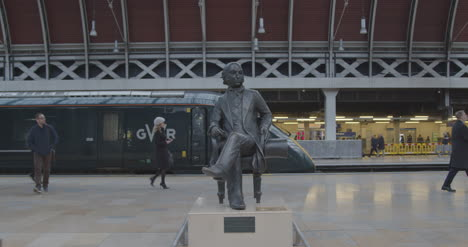 Commuters-pass-statue-on-train-platform
