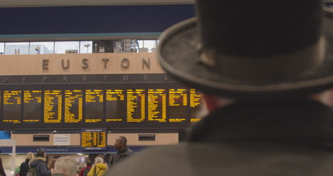 Man-wearing-hat-looking-at-Euston-Station-departure-board