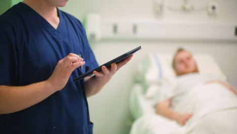 CU-Male-Nurse-Making-Notes-on-Tablet
