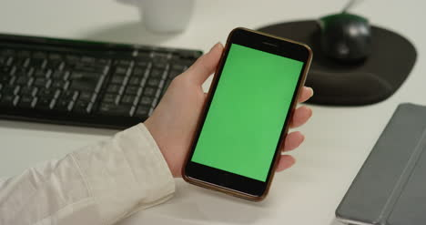 CU-Woman-at-Desk-Holds-Phone-with-Green-Screen