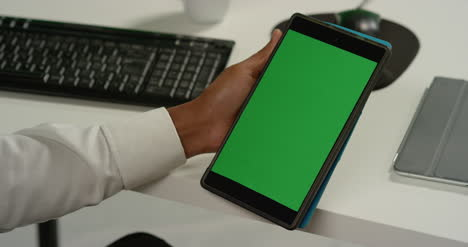 CU-Man-at-Desk-Holds-Tablet-with-Green-Screen