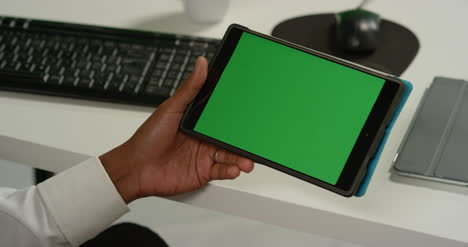 CU-Man-at-Taps-on-Tablet-with-Green-Screen