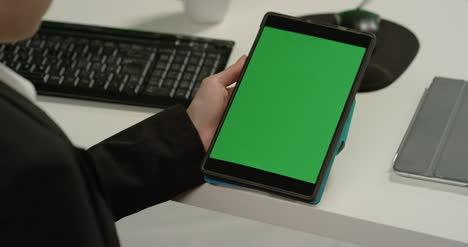CU-Woman-at-Desk-Holds-Tablet-with-Green-Screen