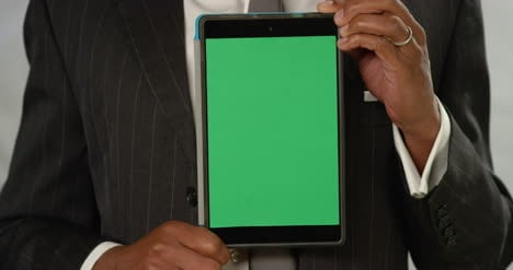 CU-Man-Holding-Tablet-at-Camera-with-Green-Screen