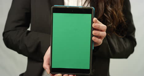 CU-Woman-Holding-Tablet-at-Camera-with-Green-Screen