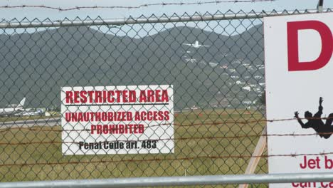 Signs-on-Airport-Perimeter-with-Plane-in-BG