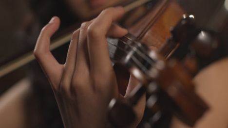 Close-Up-Violin-Scroll-And-Hand-Playing-Violin