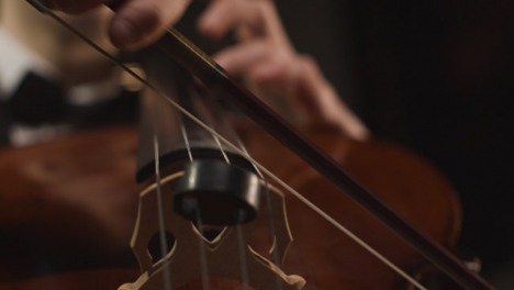 Close-Up-Hands-And-Bow-Of-Male-Cellist-Playing-Cello